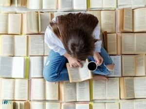 How to Set Realistic Reading Goals - Woman Sitting on a Pile of Books