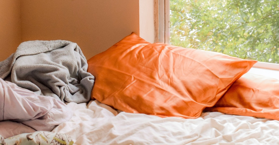 unmade bed with orange pillowcases